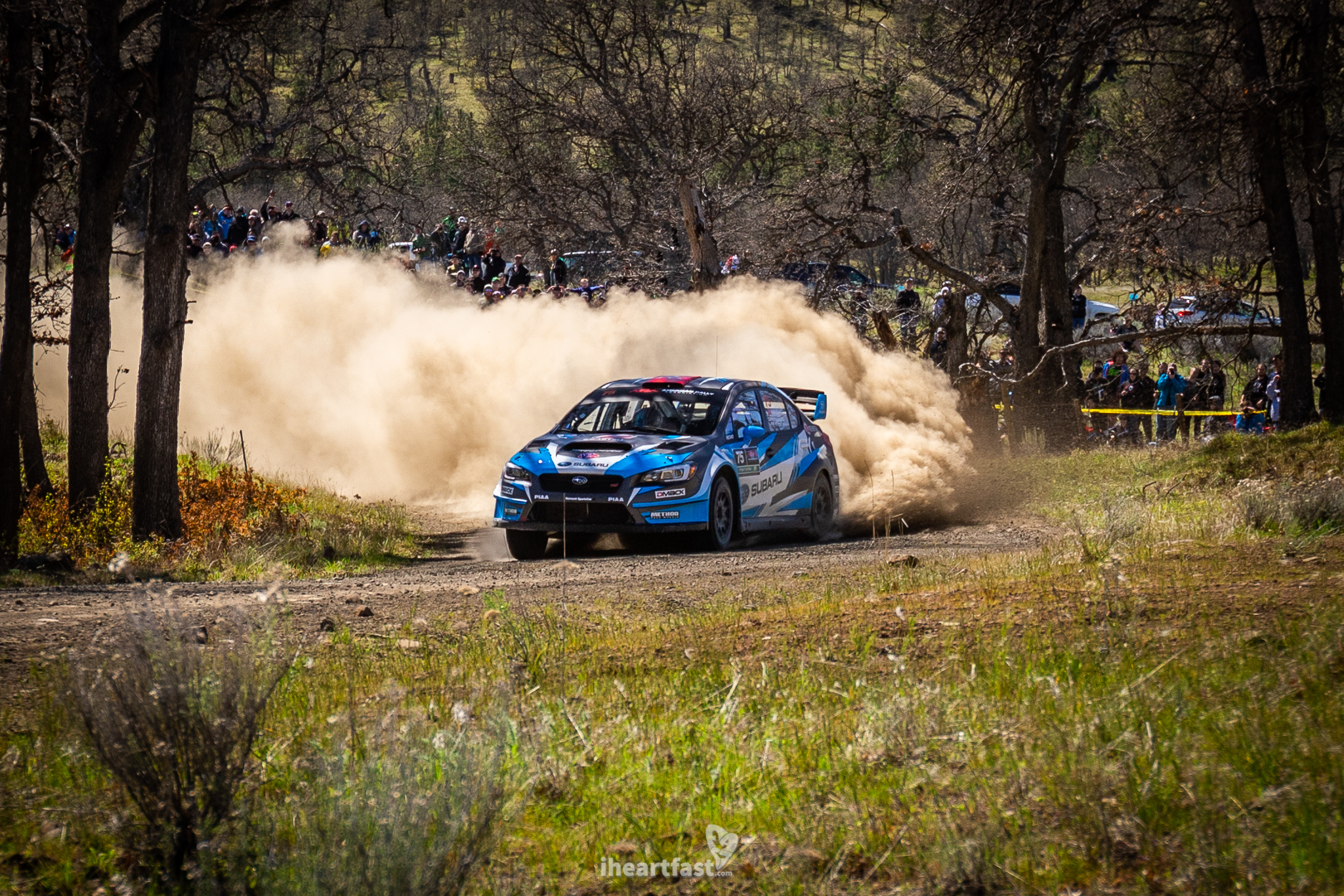 David Higgins kicks up a cloud of dust as spectators at Oregon Trail Rally cheer him on.