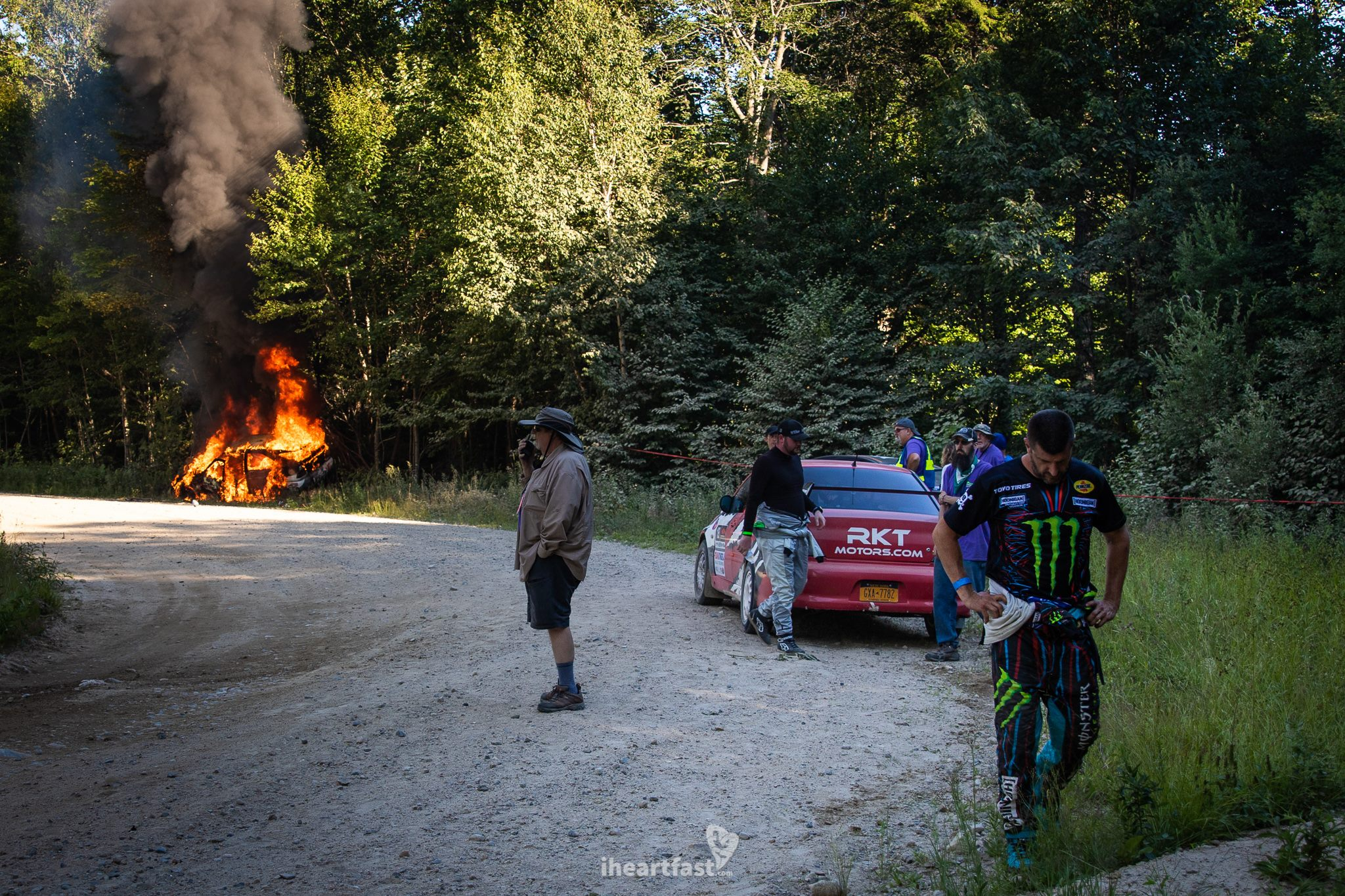 Ken Block walks away from his burning car with his head down, defeated.